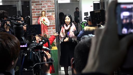 그림 2 : 영화<앨리스 죽이기>의 한 장면. 신은미씨는 토크콘서트가 끝난 후 기자회견을 진행하고 있다. 신은미씨 왼편에는 예수상이 놓여져 있다. 신은미씨 맞은편에 기자들이 카메라로 촬영하며 즐비해있고, 맨 앞쪽에는 마이크를 든 기자들이 있다.